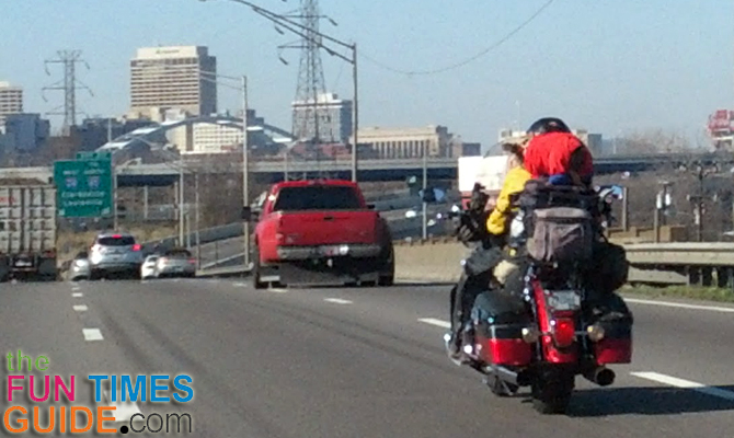 Dog riding on the back of a motorcycle. (There's another small dog riding up front near the windshield too!)